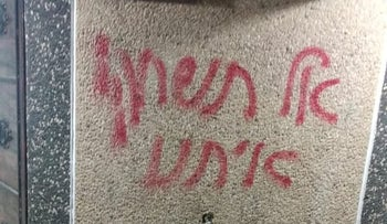 """The graffiti written on a wall near the burnt car, which reads """"Don't play with us"""" in Hebrew, West Bank village of Urif, November 13, 2018."""