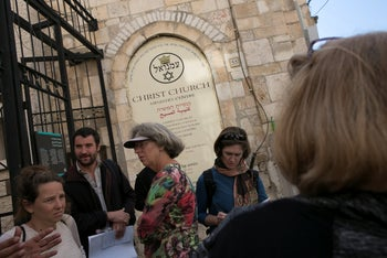 Tourists listening to their guides on the first-of-its-kind dual narrative tour of Jerusalem