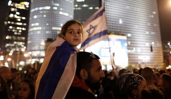 A young Israeli wears a national flag as fellow Israelis protest against a recent cease fire with the Hamas movement, in the coastal city of Tel Aviv on November 15, 2018.