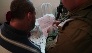 An IDF officer informs one of Ashraf Na'alwa's relatives about demolishing his home, Thursday.