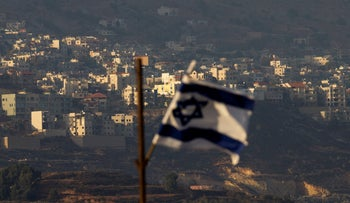 Israeli flag flutters in front of the village of Majdal Shams in the Israeli-controlled Golan Heights on October 11, 2018.