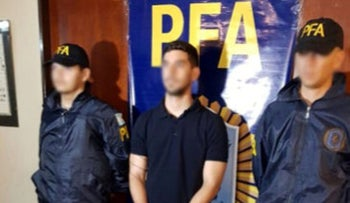 An Argentine citizen with suspected links to Hezbollah stands handcuffed and escorted by Argentine federal policemen in Buenos Aires.