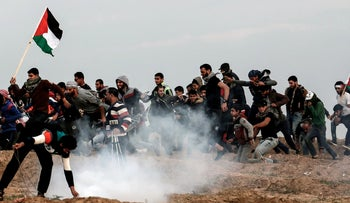 Palestinian demonstrators run for cover during a protest on November 16, 2018, on the eastern outskirts of Gaza City, near the border with Israel.