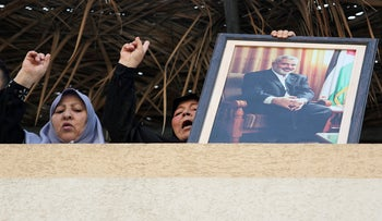 A Palestinian woman holds a picture of Hamas Chief Ismail Haniyeh as she celebrates the resignation of Israel's Defense Minister Avigdor Lieberman, in Gaza City November 14, 2018.