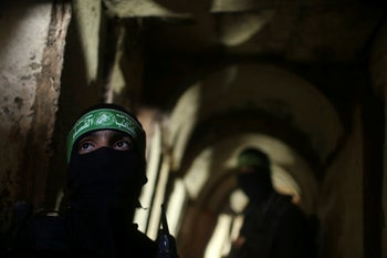 Palestinian fighters from the Izz el-Deen al-Qassam Brigades, the armed wing of the Hamas movement, stand inside an underground tunnel in Gaza. August 18, 2014