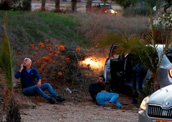 Israelis take cover as rockets are fired from the Gaza Strip, in the southern Israeli town of Sderot on November 12, 2018