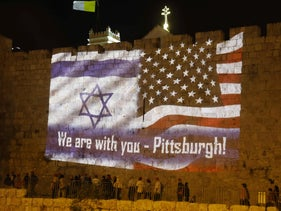 People gather under U.S. and Israeli flags projected on the walls of Jerusalem's old city on October 28, 2018, organized by the municipality to show solidarity with the Pittsburgh Jewish community