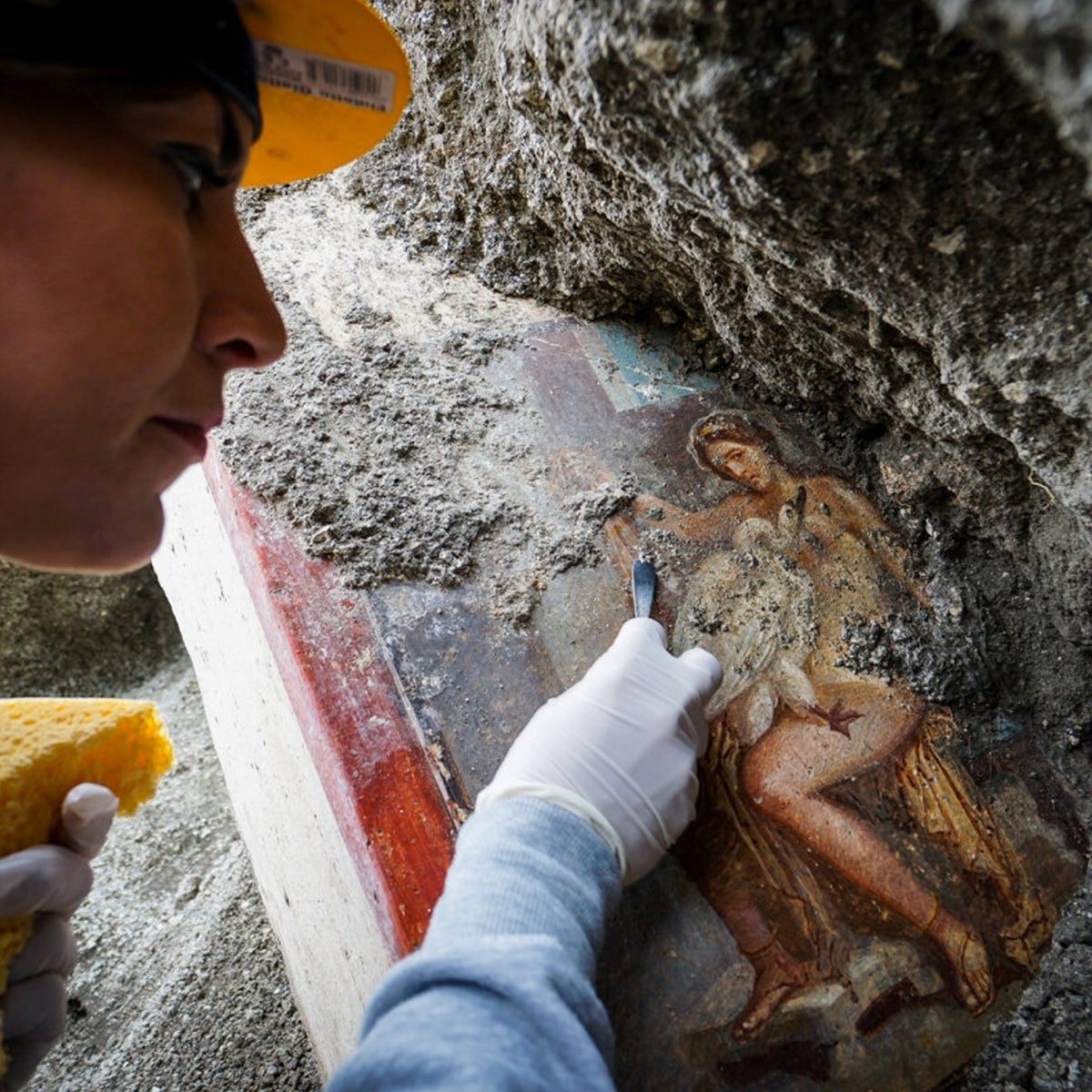 Leda and the Swan, found in Pompeii: picture shows female archaeologist wearing a yellow hat, holding a yellow sponge and scraper, working on the fresco