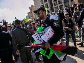 Police officers holding a confiscated Palestinian flag at a protest in May 2018.