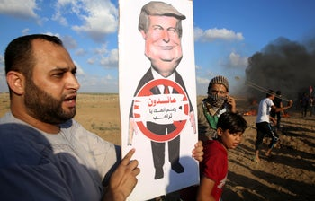 """A Palestinian protester holding a poster of President Donald Trump near the Gaza Strip border with Israel, September 7, 2018. The poster's message in Arabic says: """"We are returning in spite of you, Trump."""""""