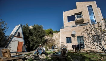 Moshe Gordon sits outside his guest house advertised on the Airbnb international home-sharing site, in the Nofei Prat settlement in the West Bank, on January 17, 2016.