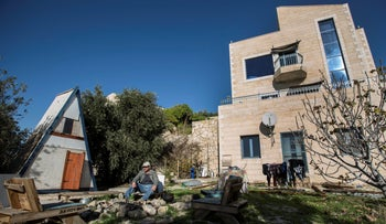 File photo: Moshe Gordon sits outside his guest house advertised on the Airbnb international home-sharing site, in the Nofei Prat settlement in the West Bank, Jan. 17, 2016.