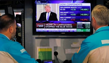 Specialists on the floor of the New York Stock Exchange watch President Donald Trump's news conference Wednesday, Nov. 7, 2018