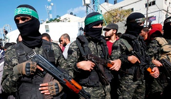 Palestinian militants of the Islamist movement Hamas' military wings attend the funeral of seven Palestinians killed during an Israeli special forces operation in the Gaza Strip, on November 12, 2018.