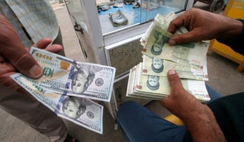 FILE PHOTO: Iranian rials, U.S. dollars and Iraqi dinars at a currency exchange shop in Basra, Iraq, November 3, 2018.