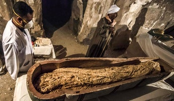 """Egyptian workers and archaeologists standing next to an opened intact sarcophagus containing a well-preserved mummy of a woman named """"Thuya,"""" November 24, 2018."""