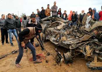 Palestinians inspect the remains of a vehicle destroyed in an Israeli air strike, Khan Younis, southern Gaza Strip November 12, 2018.