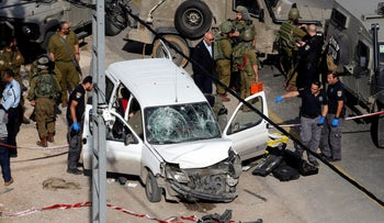 Israeli policemen inspect the scene of a car ramming attack near Hebron, in the occupied West Bank November 26, 2018.