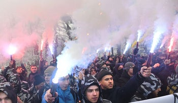 Activists of Ukrainian far-right groups hold flares during their rally in front of the Ukrainian parliament in Kiev on November 26, 2018, as they demand to set martial law in the country and to cut diplomatic relations with Russia