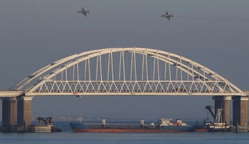 Russian jet fighters fly over a bridge connecting the Russian mainland with the Crimean Peninsula with a cargo ship beneath it after three Ukrainian navy vessels were stopped by Russia from entering the Sea of Azov via the Kerch Strait in the Black Sea, Crimea November 25, 2018