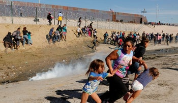 A migrant mother and her children flee tear gas at the U.S. border with Mexico, Tijuana, November 25, 2018.
