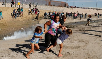 A migrant family, part of a caravan of thousands traveling from Central America to the United States, run away from tear gas in front of the border wall between the U.S. and Mexico in Tijuana, Mexico, November 25, 2018.