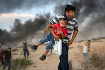 A Palestinian protester carries a boy as he runs from tear gas fired by Israeli soldiers during a protest, Israel-Gaza border, September 10, 2018.
