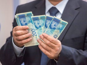 A man holding 200 shekels notes