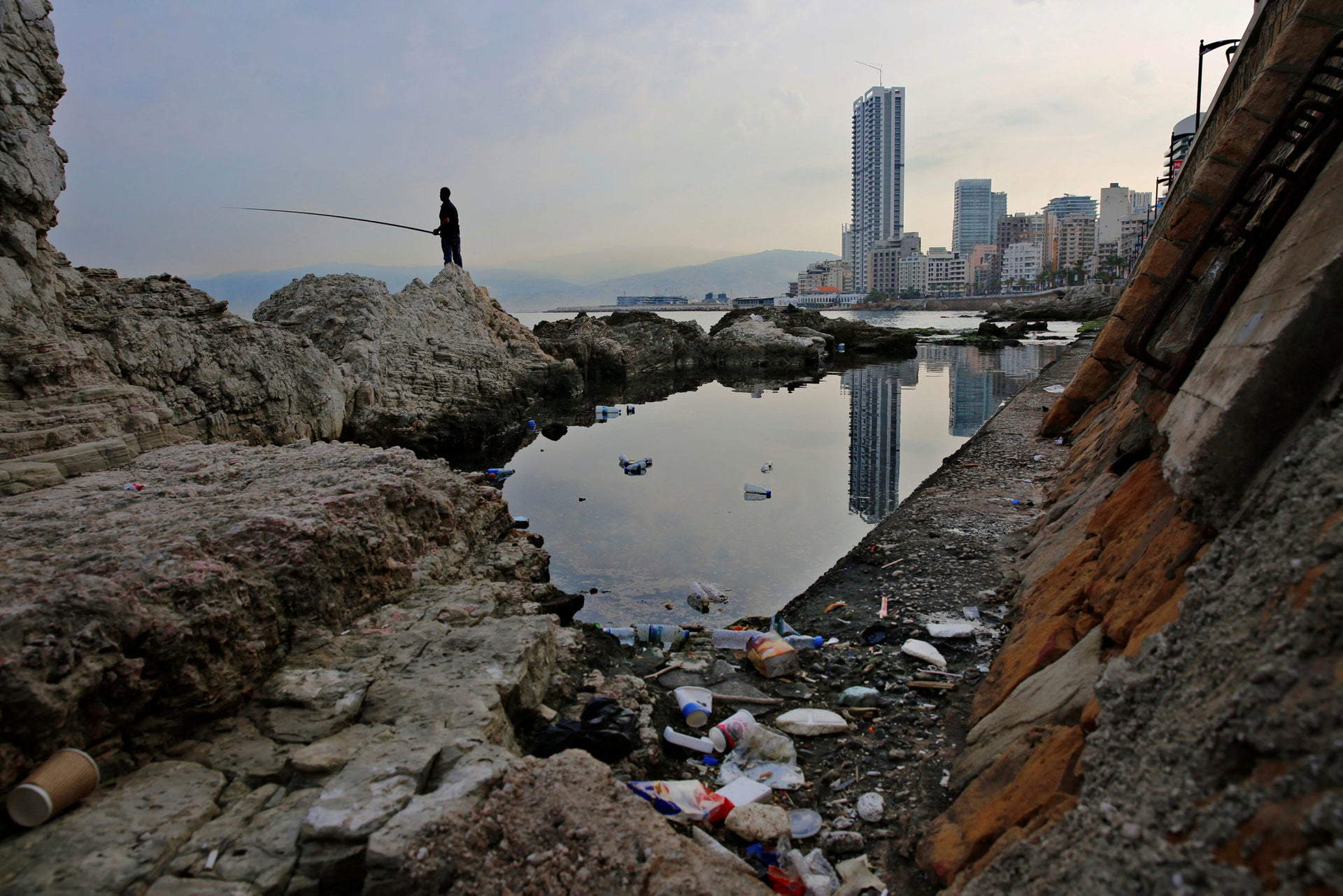 "In this Wednesday, Nov. 14, 2018 photo, a man casts his fishing pole in the Mediterranean Sea as trash are seen on a rocky coastal area along the Beirut coastline, Lebanon. Fisherman Ahmad Obeitri, who has been a fixture at Lebanon's corniche for the past 30 years, says the trash is killing off what's left of marine life. ""These days if a fish comes our way it will only find nylon bags, garbage and sewage to feed on,"" he said, lamenting the people who eat and drink as they walk on the corniche and then toss their cans, tins and other containers in the sea. ""You can open a cafe under water and invite your friends,"" he adds sarcastically."