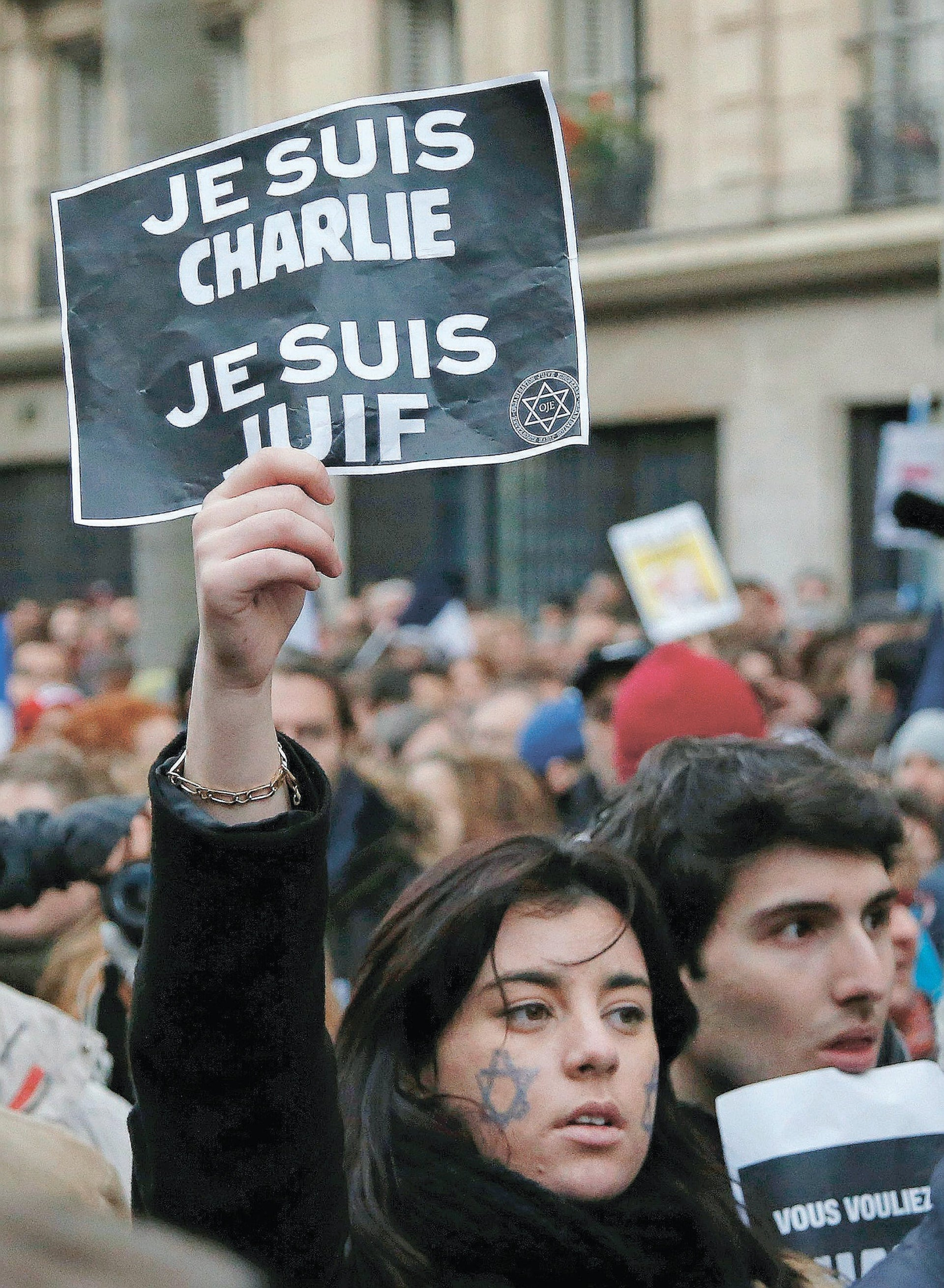 """A demonstrator holds a sign reading """"I am Charlie, I am Jewish"""" during a rally in Paris,  Jan. 11, 2015."""