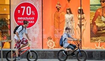 Youngsters ride past a sign written in Russian, that advertises price cuts in Chisinau, Moldova., on August 22, 2018.