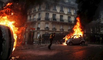 Protesters walk by burning cars during clashes with riot police on the sideline of a protest of Yellow vests (Gilets jaunes) against rising oil prices and living costs, on December 1, 2018 in Paris