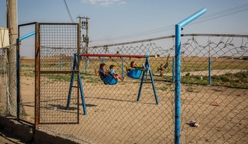 Youths play on swings at Roj Camp for the families of Islamic State members in Kurdish-controlled northern Syria, June 23, 2018.