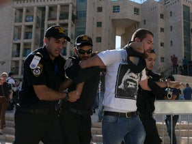 A demonstrator being led away by Israeli police officers during a demonstration against the opening of the U.S. Embassy in Jerusalem, May 13, 2018.