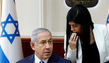 File photo: Israeli Prime Minister Benjamin Netanyahu listens to an advisor during the weekly cabinet meeting at his office in Jerusalem, December 2, 2018.