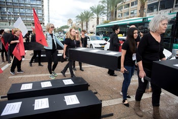 Women carrying black coffins to represent the 24 women and girls murdered by partners, family or people they knew, Tel Aviv, December 4, 2018.