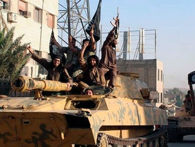 File photo: Fighters from the Islamic State group ride tanks during a parade in Raqqa, Syria, posted by the Raqqa Media Center in Islamic State group-held territory, on June 30, 2014.