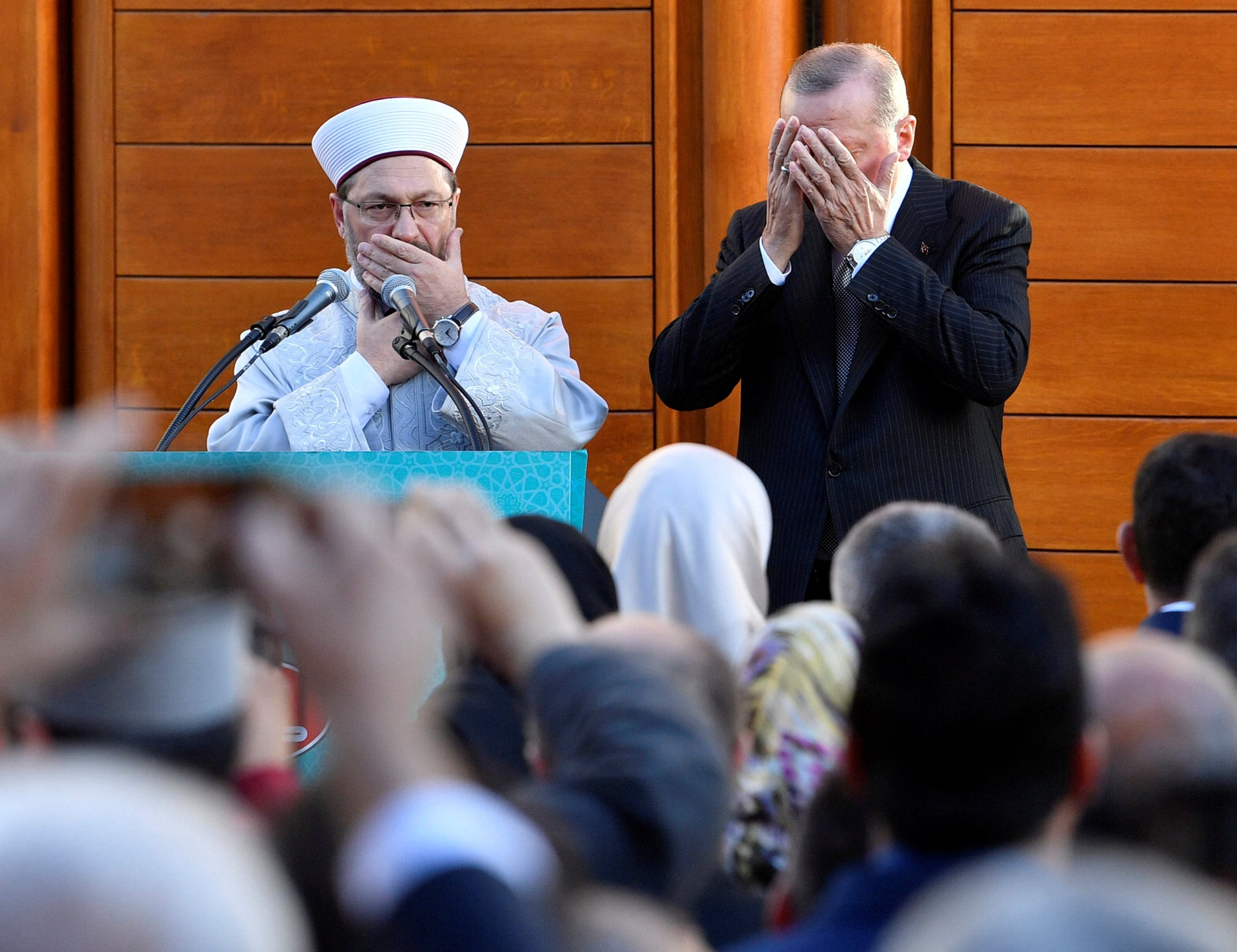 Turkish President Recep Tayyip Erdogan and Diyanet President Ali Eras cover their faces during a prayer on occasion of the opening of the new mosque in Cologne, Germany, on Saturday, Sept. 29, 2018.