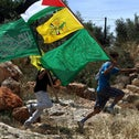 Palestinian protesters carrying the Hamas (bottom) and Fatah (center) flags during a rally in the West Bank village of Bil'in.