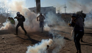 Migrants from Central America and journalists being hit by tear gas after hundreds tried to illegally cross the Mexico border into the United States, Tijuana, Mexico, November 25, 2018.