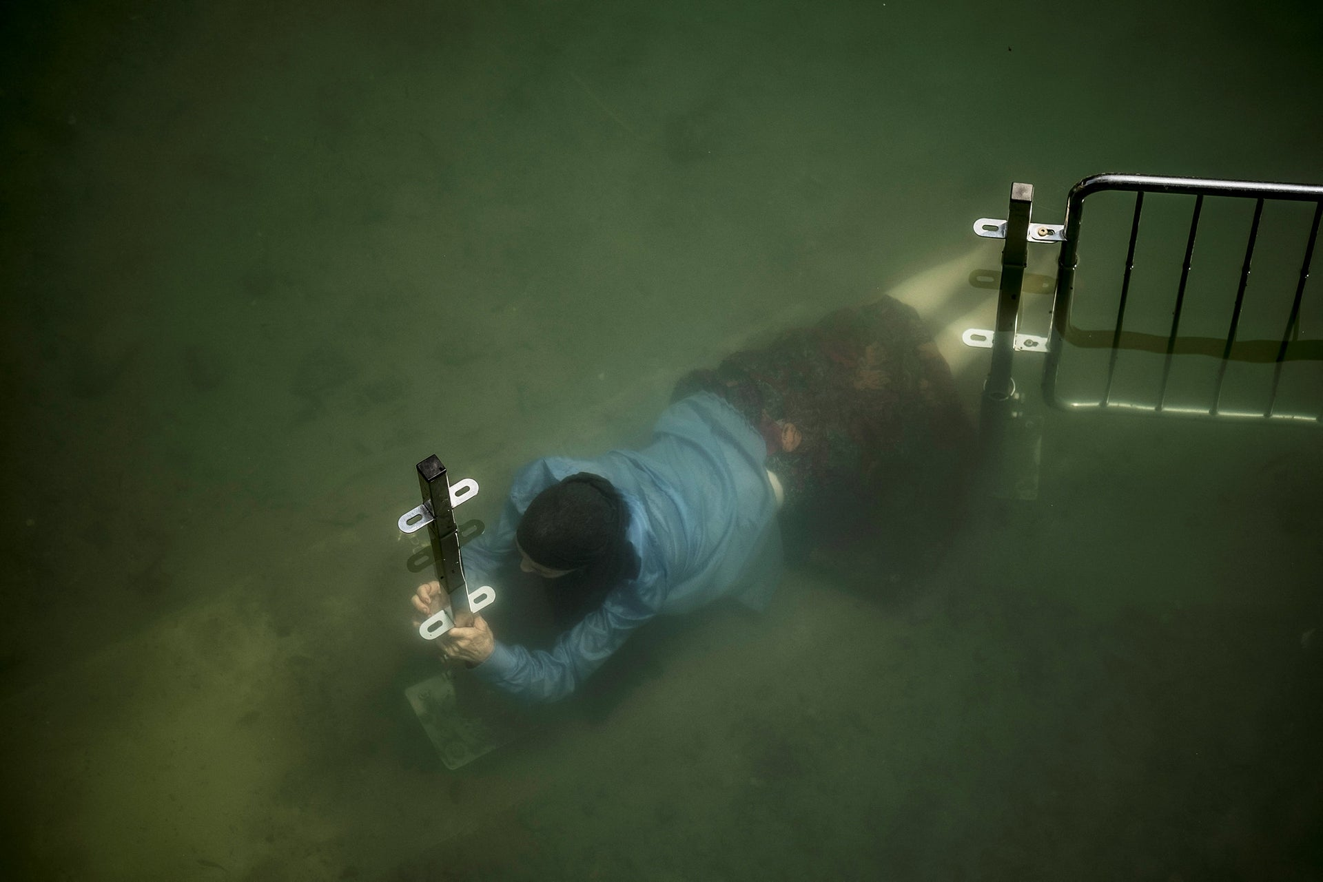 FILE PHOTO: A Christian pilgrim submerges herself in the Jordan river