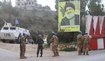 UN peacekeepers stand in front a poster of Hezbollah leader Sheik Hassan Nasrallah in the southern village of Kfar Kila, Lebanon, December 4, 2018