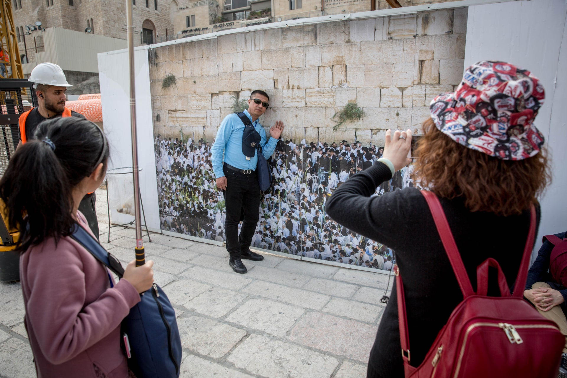 File photo: A man has his picture taken in front of an image of the Western Wall in Jerusalem.