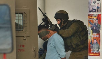 An Israeli soldier arresting a Palestinian in the West Bank.