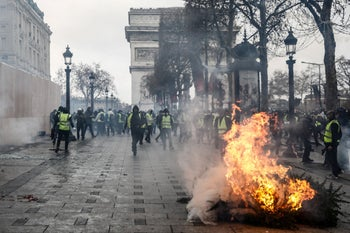 Protesters wearing yellow vests (gilets jaunes) stand near the Arc de Triomphe on the Champs-Elysees avenue in Paris, on December 8, 2018.