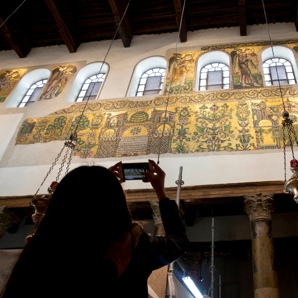 In this Thursday, Dec. 6, 2018 photo, a visitor photographs a renovated part of a fresco inside the Church of the Nativity, built atop the site where Christians believe Jesus Christ was born, in the West Bank City of Bethlehem. City officials are optimistic that the renovated church will help add to a recent tourism boom and give a boost to the shrinking local Christian population.