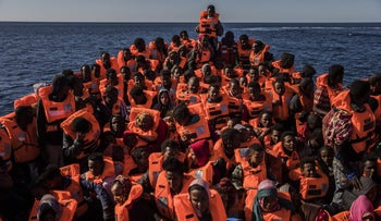 Asylum seekers on a rubber boat leaving from the coast of Libya to Europe.