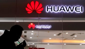 A man lighting a cigarette outside a Huawei retail shop in Beijing, December 6, 2018.