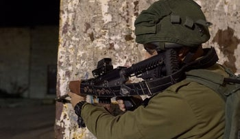 Israeli soldier seen during manhunt for assailants who carried out a drive-by shooting attack in the West Bank.