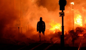 A Gilets Jaunes/Yellow Vest protestor stands near a fire in Bordeaux, southwestern France, on the sidelines of a protests against rising living costs.December 8, 2018